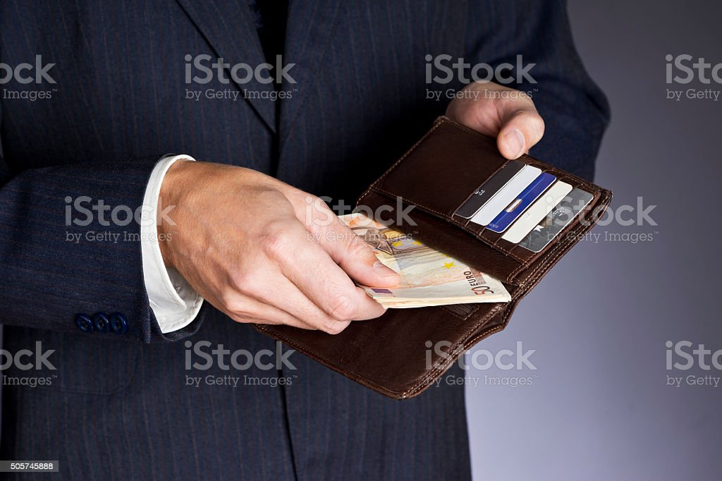 Business man putting banknotes, fifty euros, credit cards in wallet. stock photo
