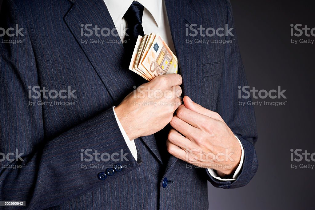Business man putting banknotes  (fifty euros)  in his jacket pocket stock photo
