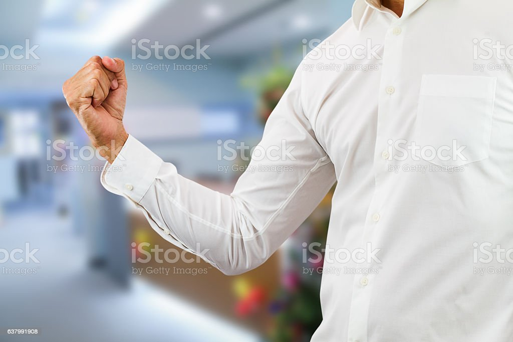 Business man raising right fist up with cheerful in office stock photo