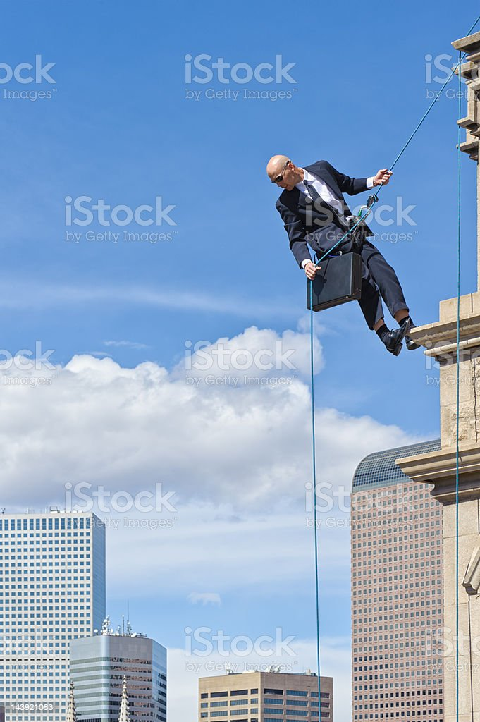 Business Man Rappelling Off High Building stock photo