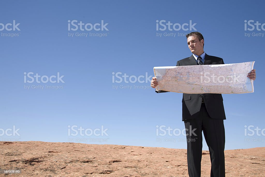 Business man reading a map in desert stock photo
