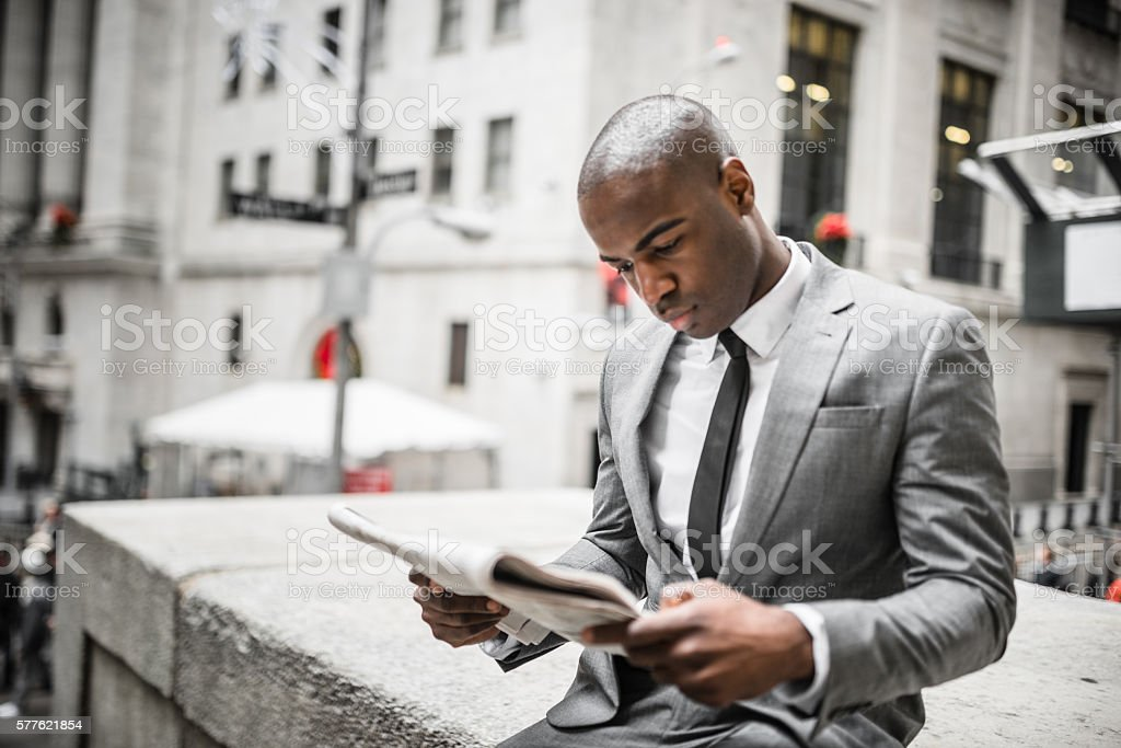 business man reading a newspaper on nyc stock photo