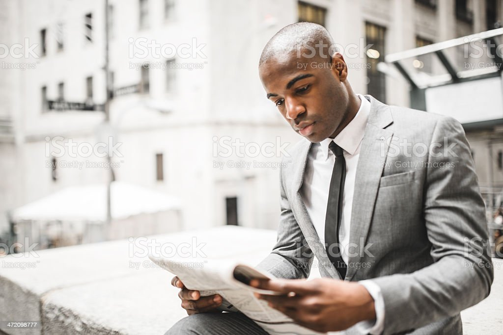 business man reading a newspaper on wall street stock photo