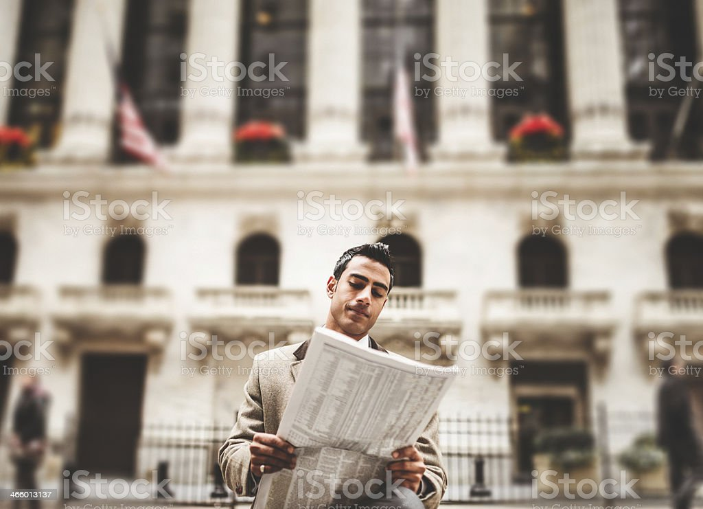 business man reading a newspaper sitting on wall street stock photo