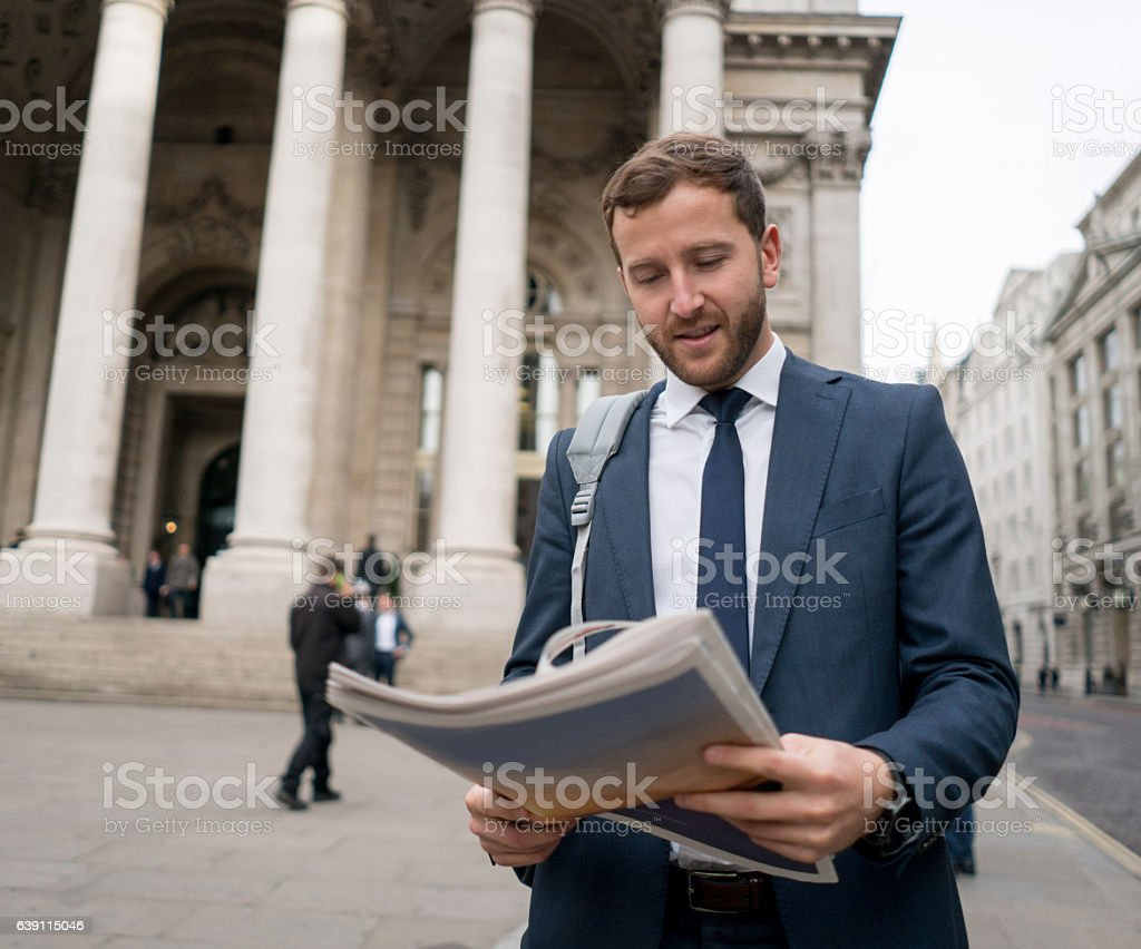 Business man reading the newspaper in the street stock photo