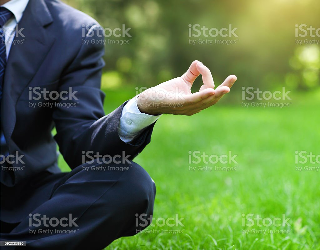Business man relax in a park lotus position stock photo
