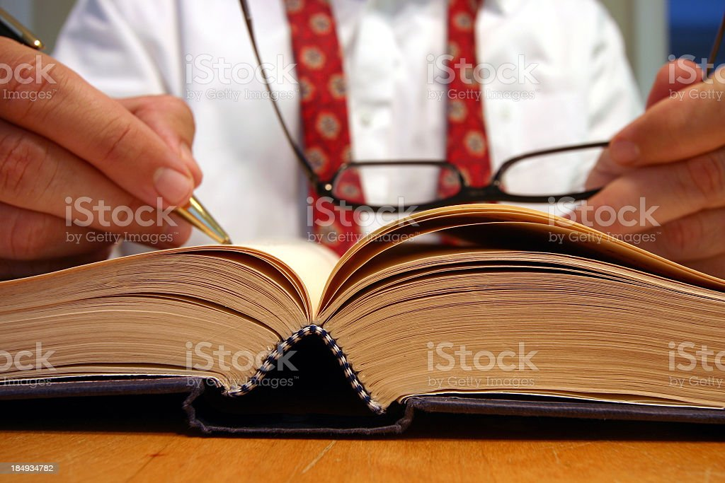 Business man researching and making notes from a book  stock photo