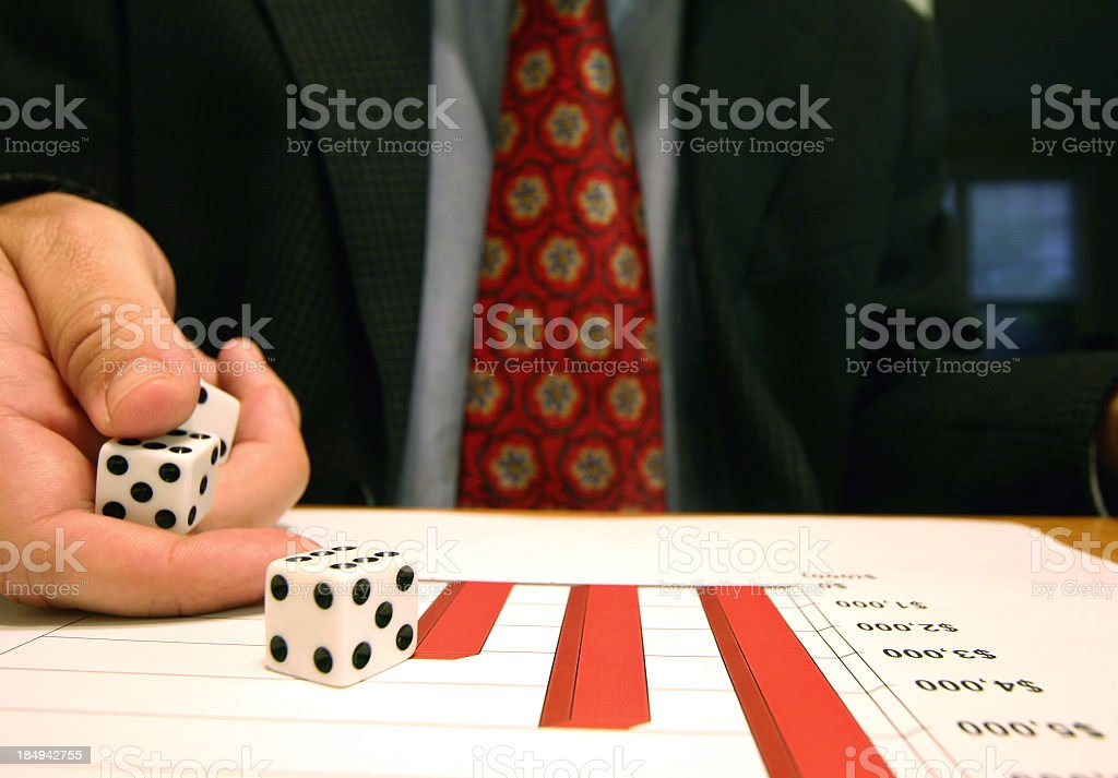 A business man rolling dice on a graph of profits stock photo