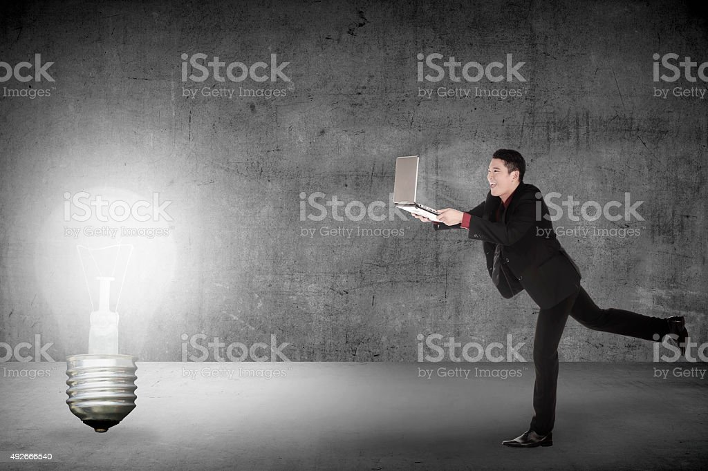 Business man run with laptop chasing light bulb stock photo