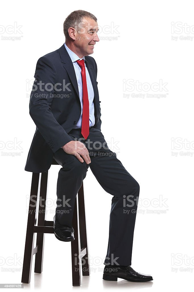 business man sits and smiles stock photo