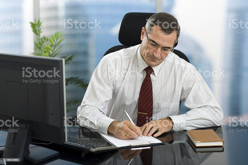 Business man sitting at his glossy desk filling out a note royalty-free stock photo