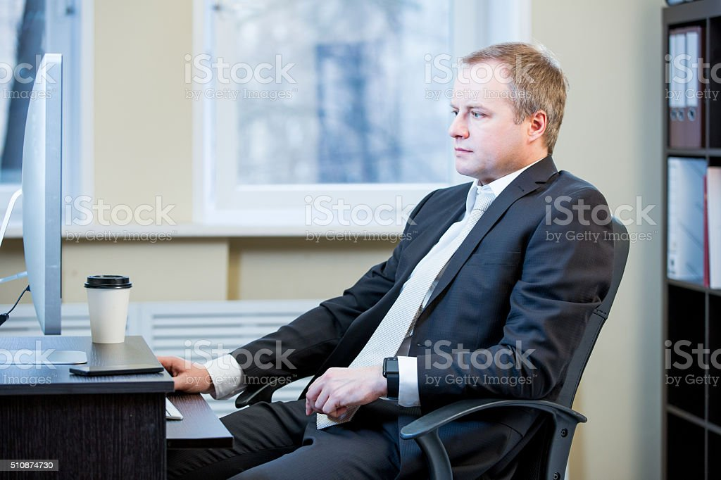 Business man sitting at the office desk stock photo