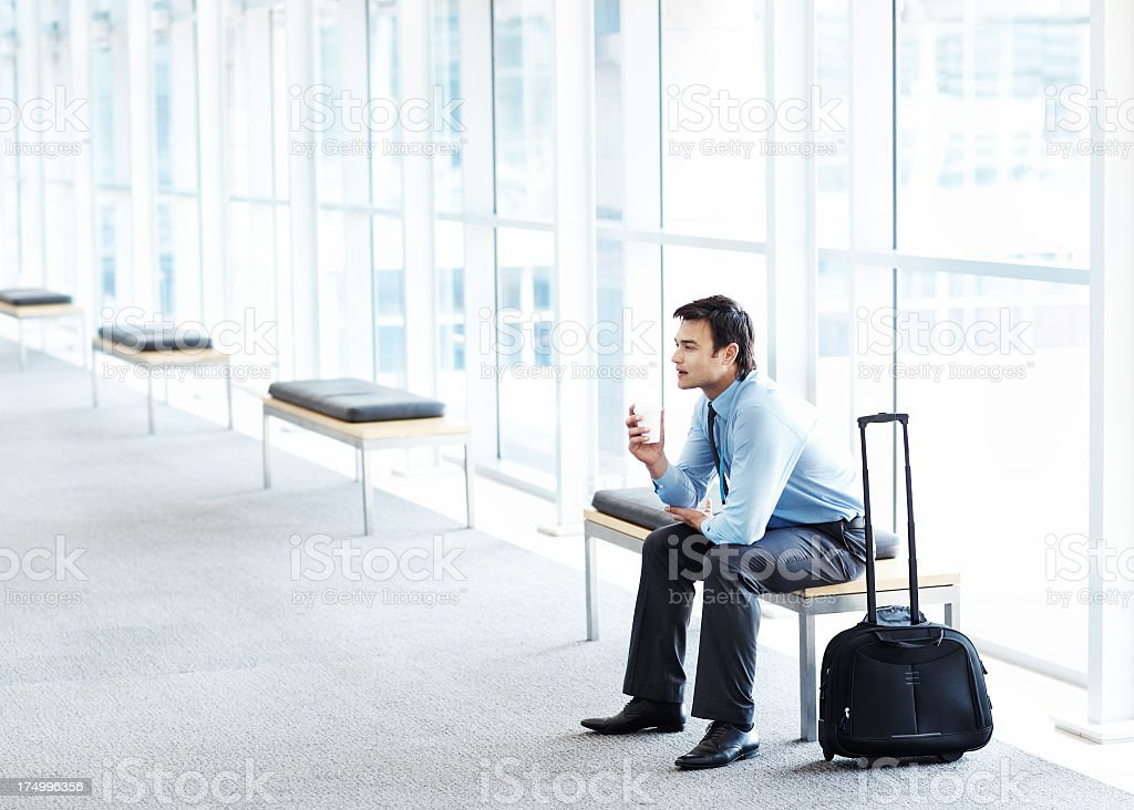 Business man sitting in an empty hallway with his briefcase royalty-free stock photo
