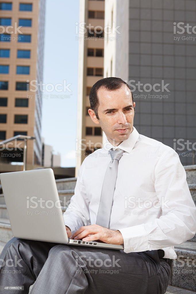 Business man sitting on steps using laptop stock photo