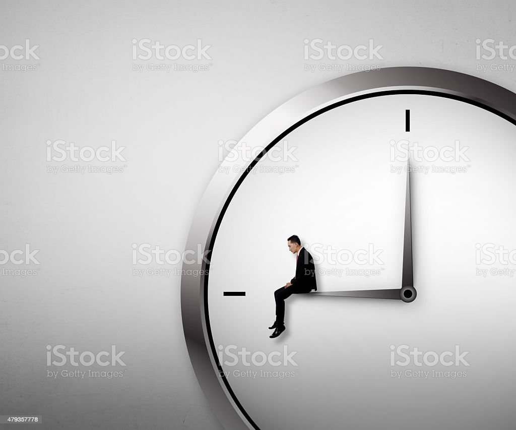 Business man sitting on the clock stock photo