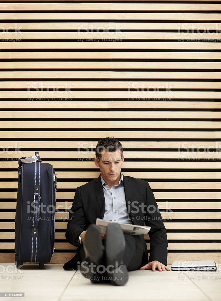 Business man sitting on the floor reading newspaper stock photo