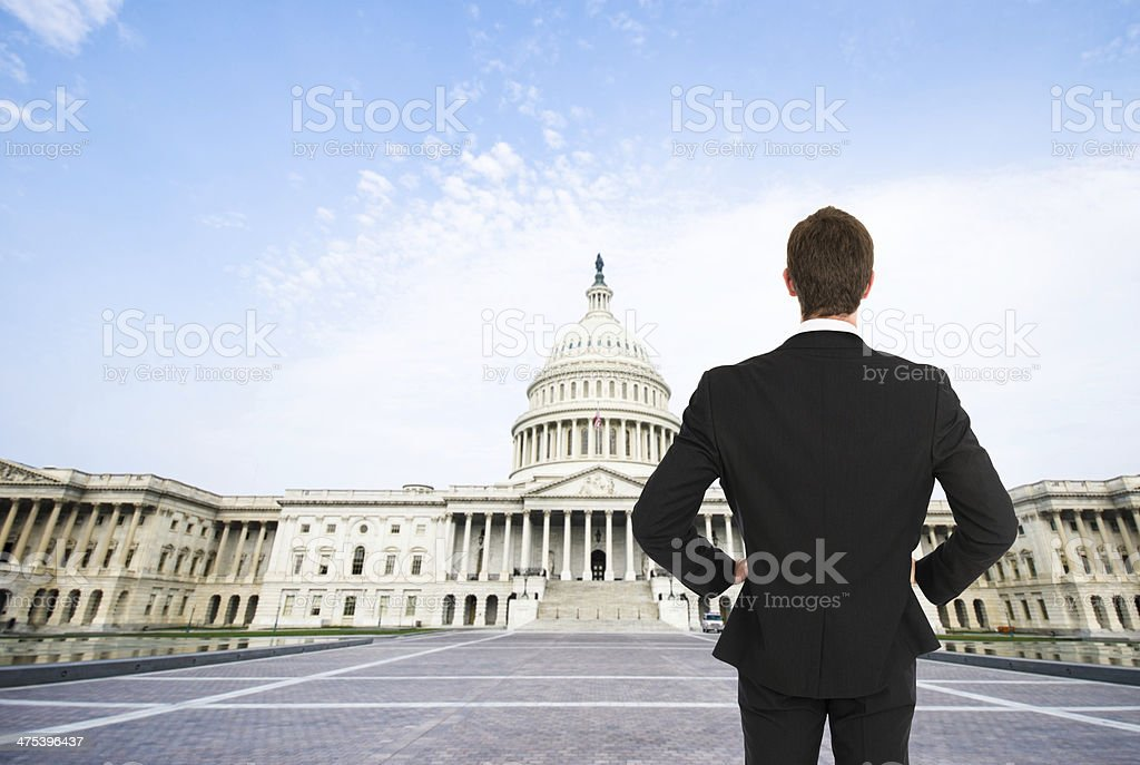Business man standing in front of capitol hill stock photo