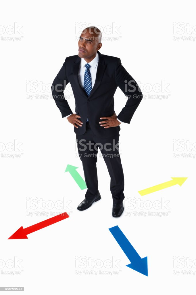 Business man standing in the middle of colorful arrows royalty-free stock photo