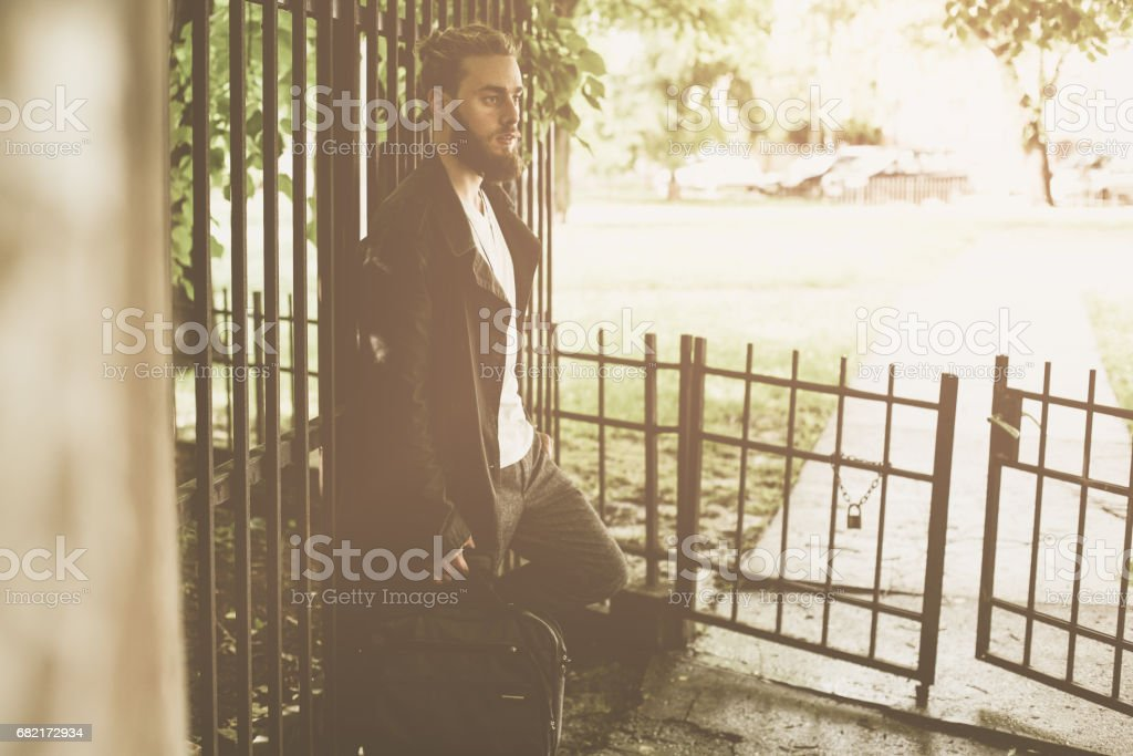Business man standing in the park. Alone man resting. stock photo