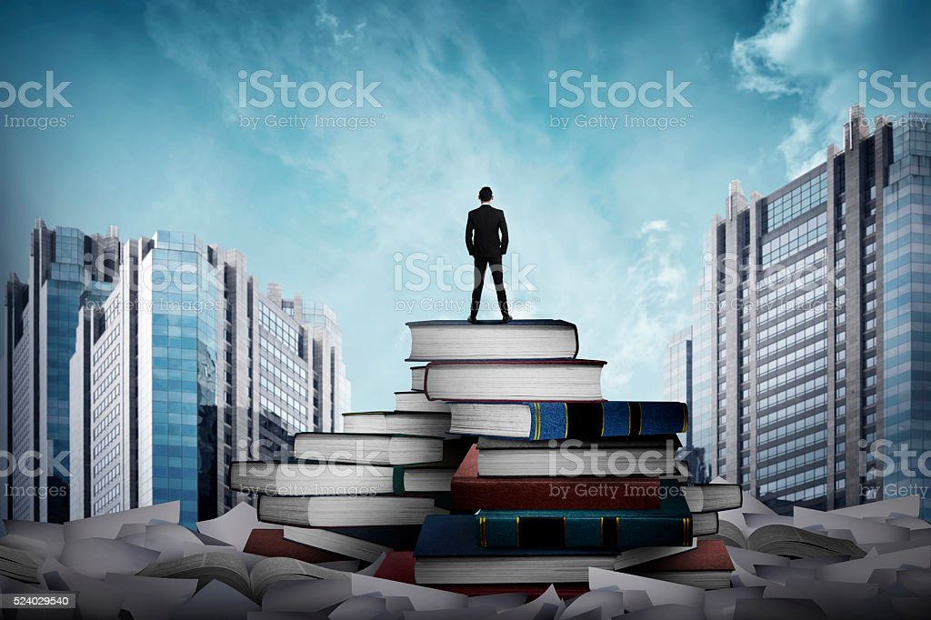 Business man standing on the top of books stock photo