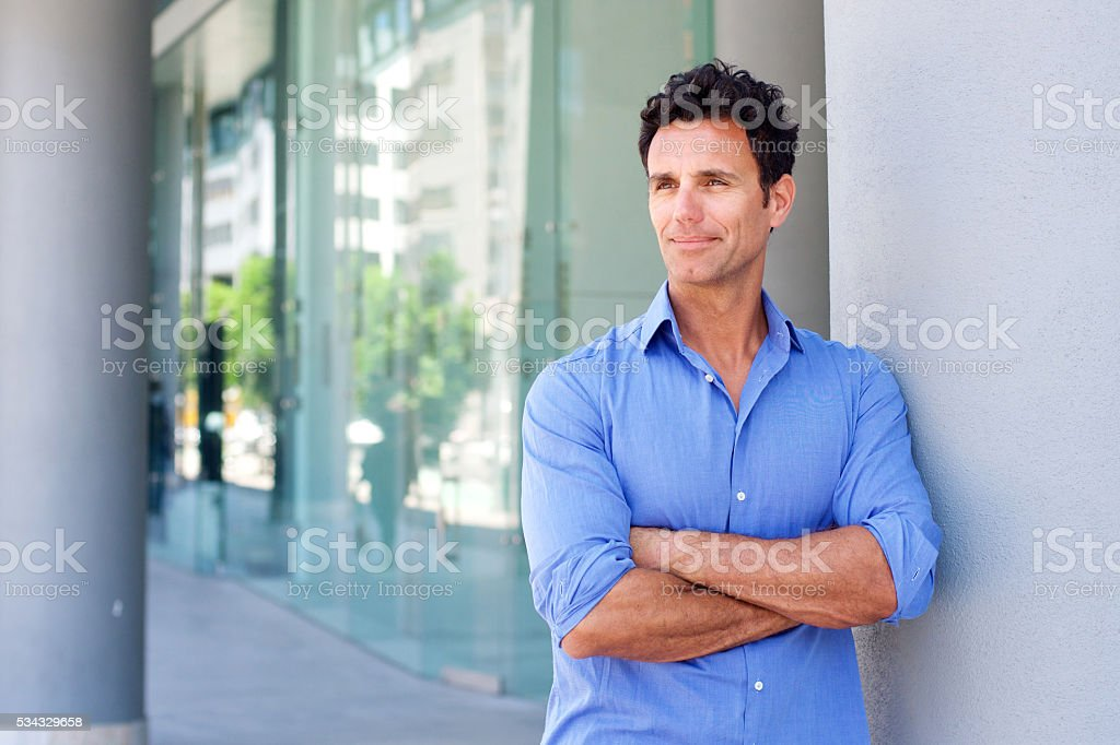 Business man standing outside with arms crossed stock photo