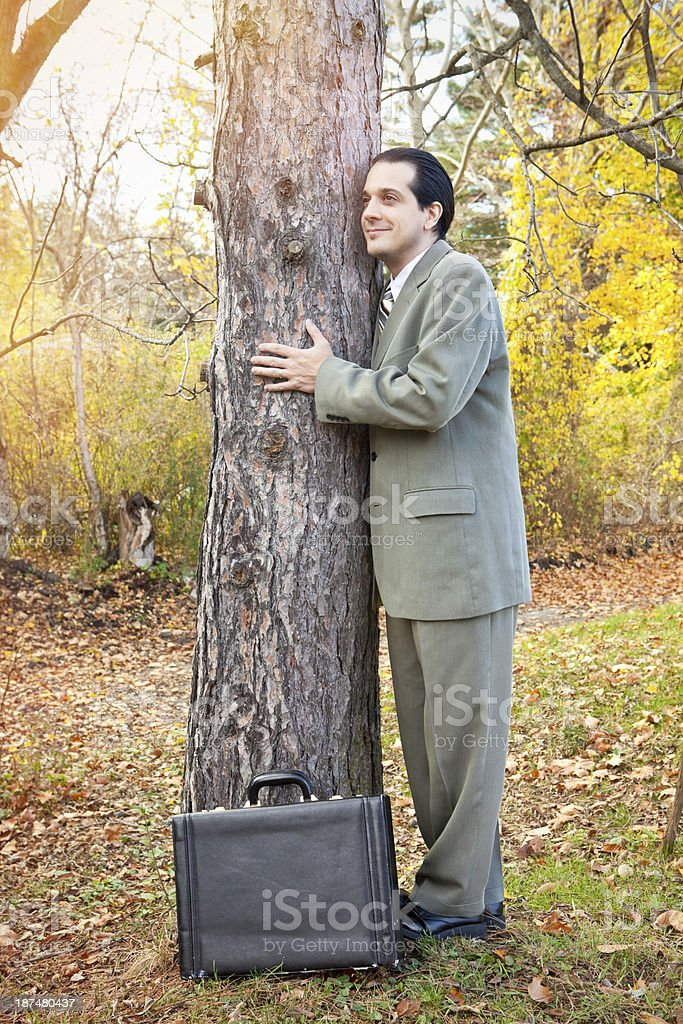 Business Man Stopping To Hug A Tree royalty-free stock photo