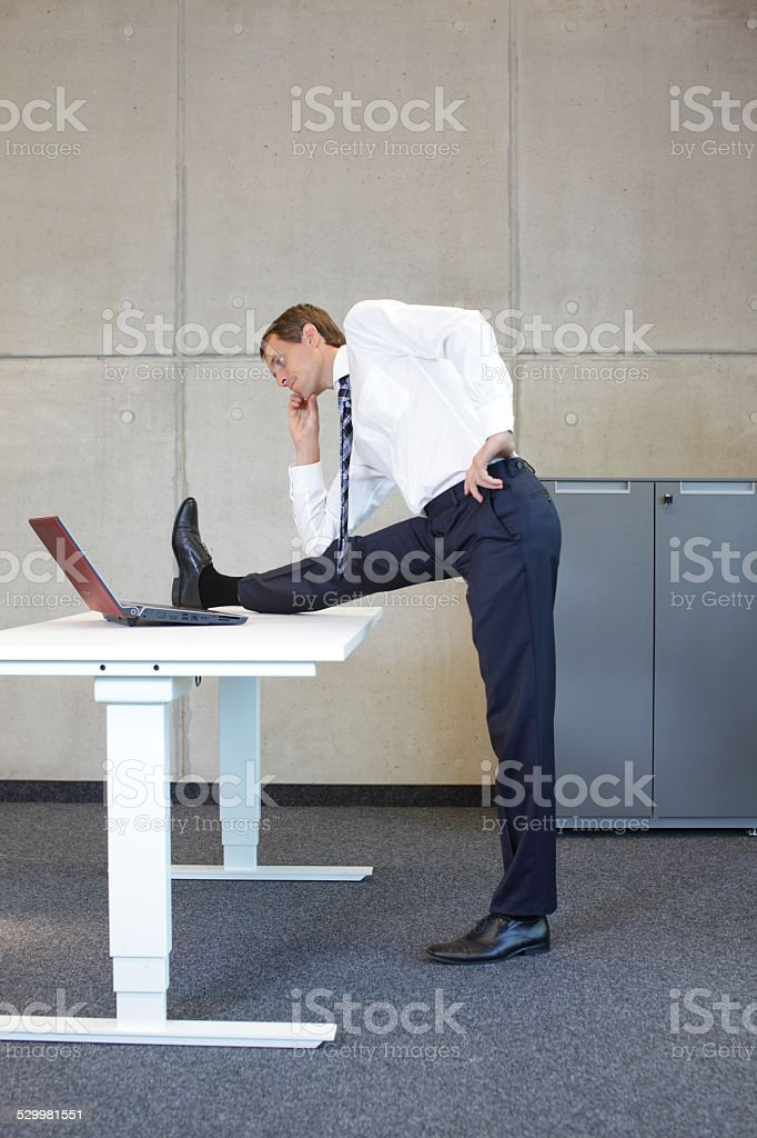 business man stretching in standing position at desk leg stock photo