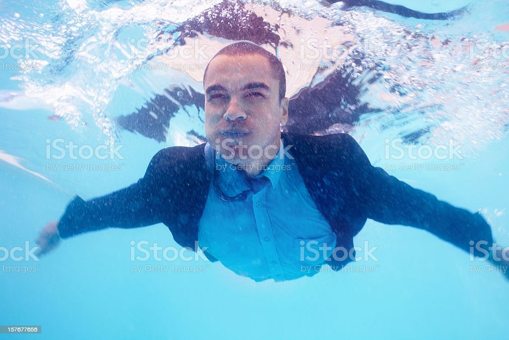 Business man swimming under water in pool wearing a suit stock photo