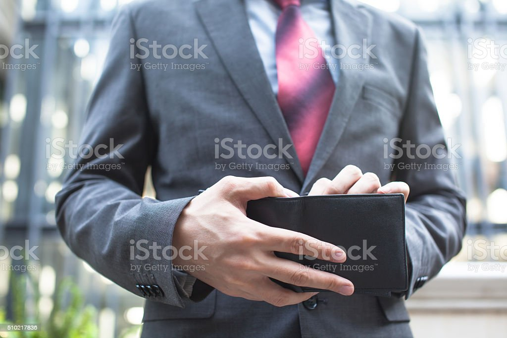 Business man taking bills out of wallet stock photo