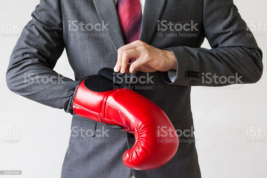 Business man taking off boxing gloves as he gives up stock photo