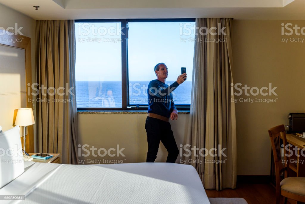 Business man taking selfies on his mobile phone by the window in his hotel room stock photo