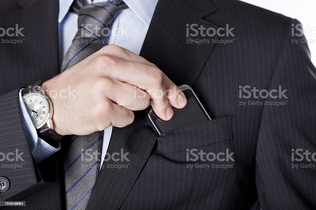 Business man taking the smartphone out of his pocket stock photo