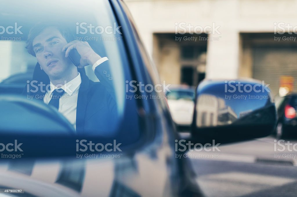 Business man talking at the mobile phone inside a car stock photo