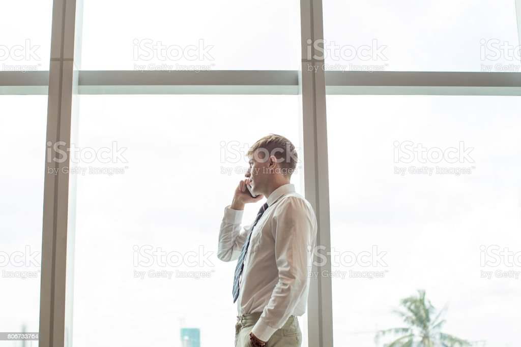 Business Man Talking on Phone at Window stock photo