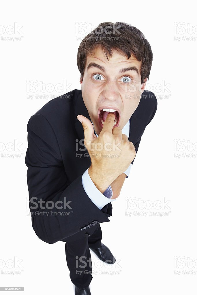 Business man teasing with finger in mouth stock photo