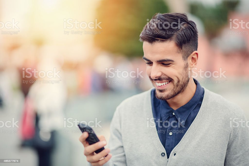 Business man texting on smartphone outside stock photo
