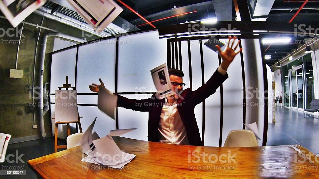 Business man throwing paperwork in frustration stock photo