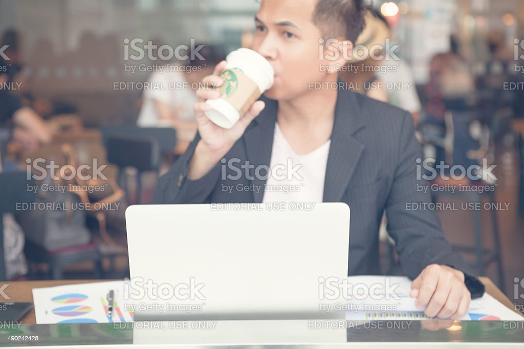Business man to drinking starbucks and working stock photo