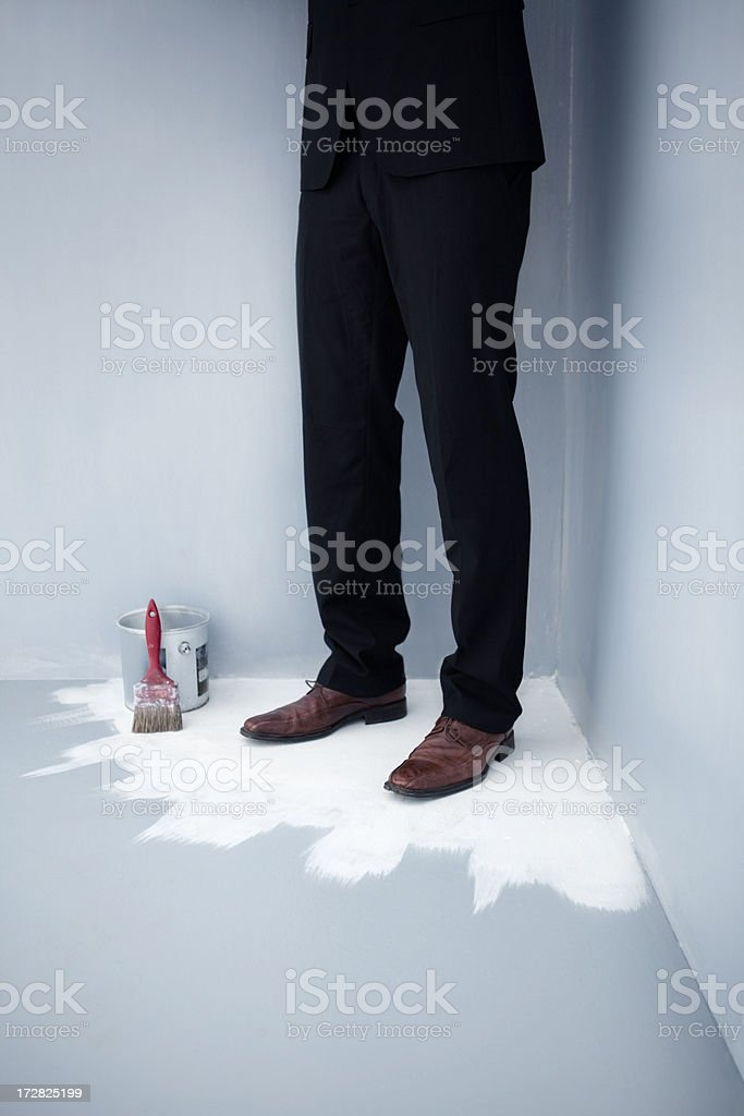 Business man trapped at the corner of a painted floor stock photo