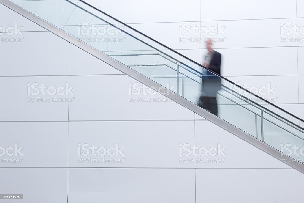 Business man travels up the escalator royalty-free stock photo