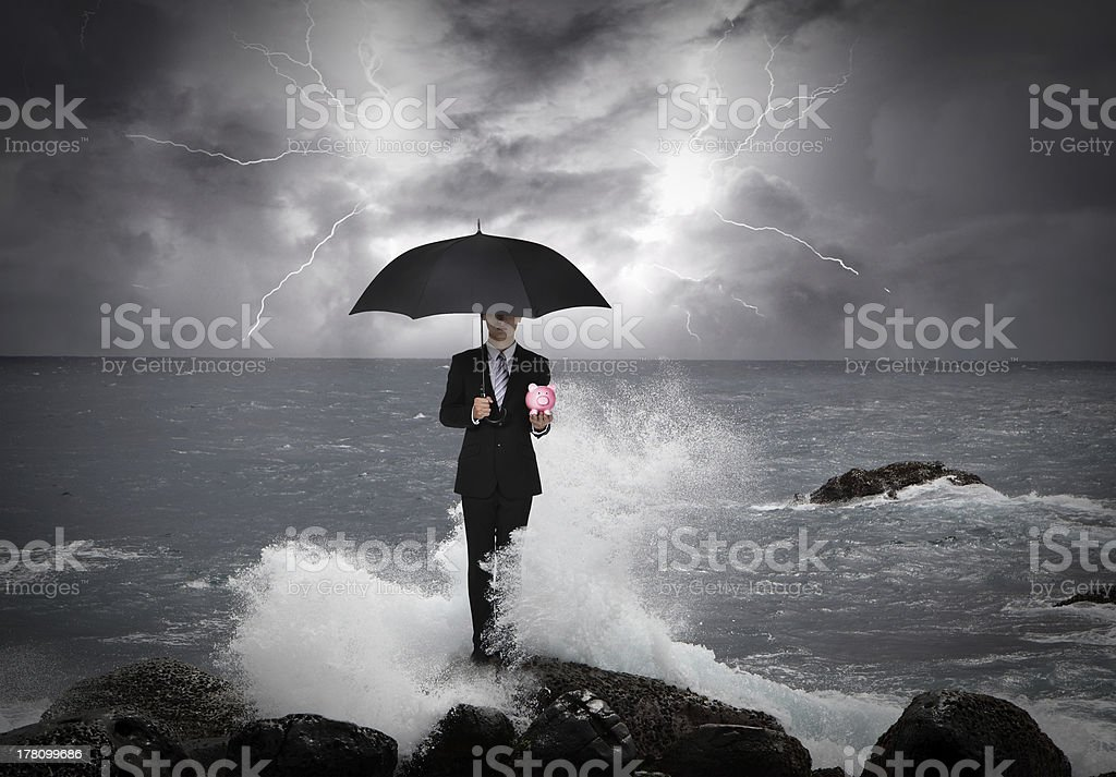 Business man under an umbrella in the sea stock photo