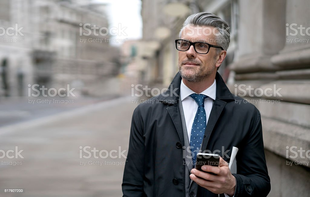 Business man using his cell phone on the street stock photo