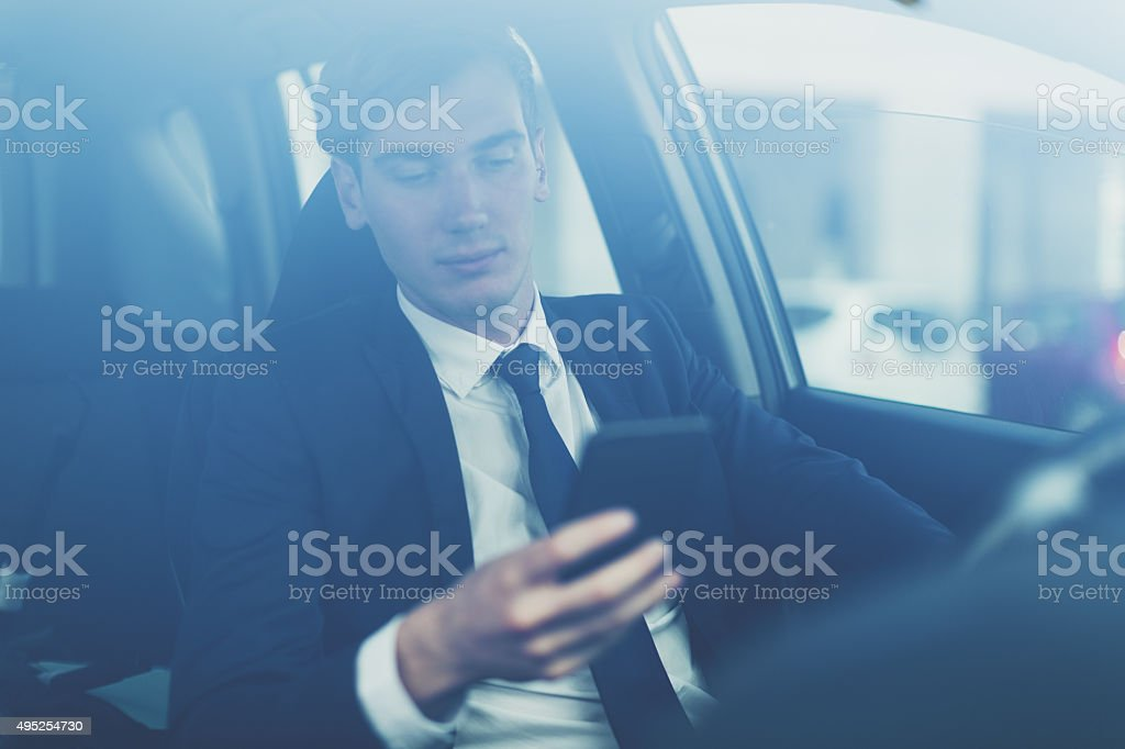 Business man using mobile phone inside a car stock photo