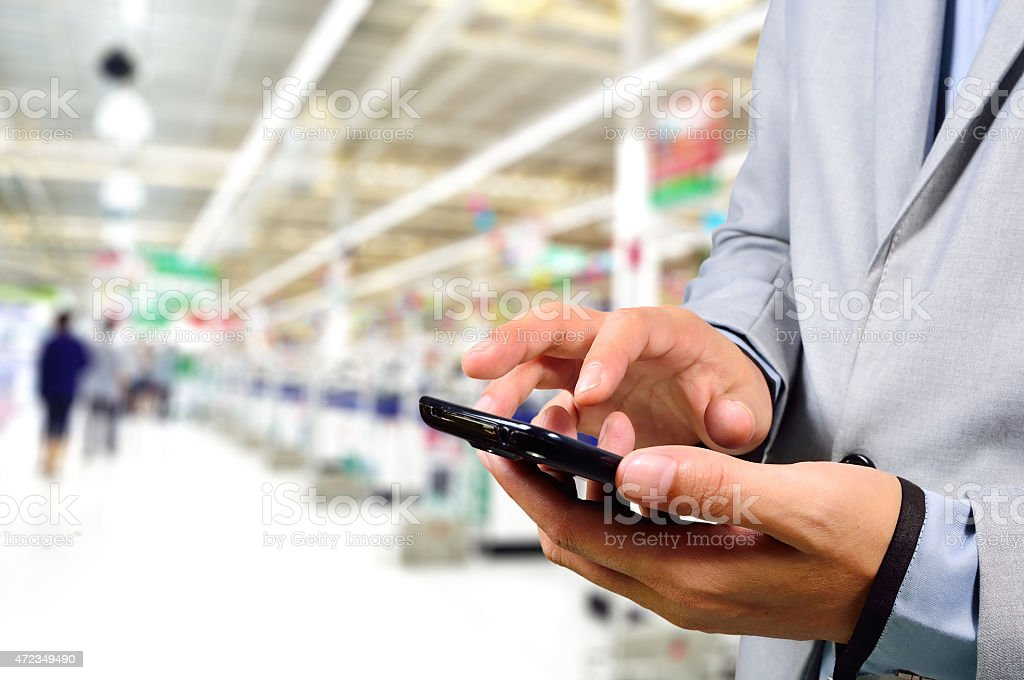 Business Man using mobile phone while shopping in supermarket. stock photo