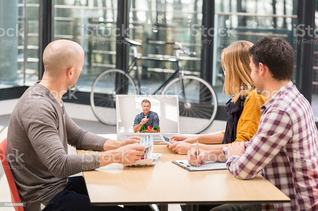 Business man Videochatting With Colleagues On Computer stock photo