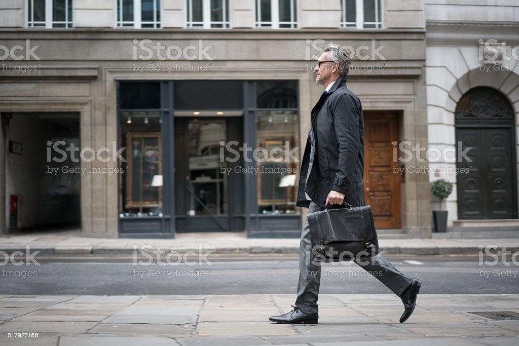 Business man walking down the street stock photo