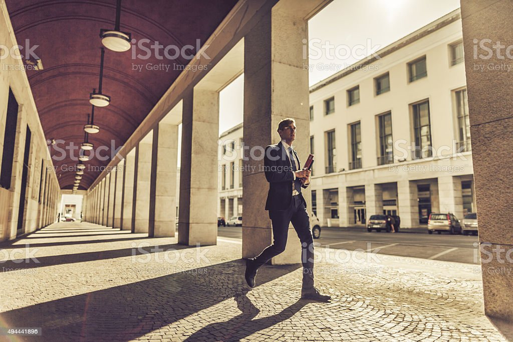 Business man walking in a colonnade stock photo