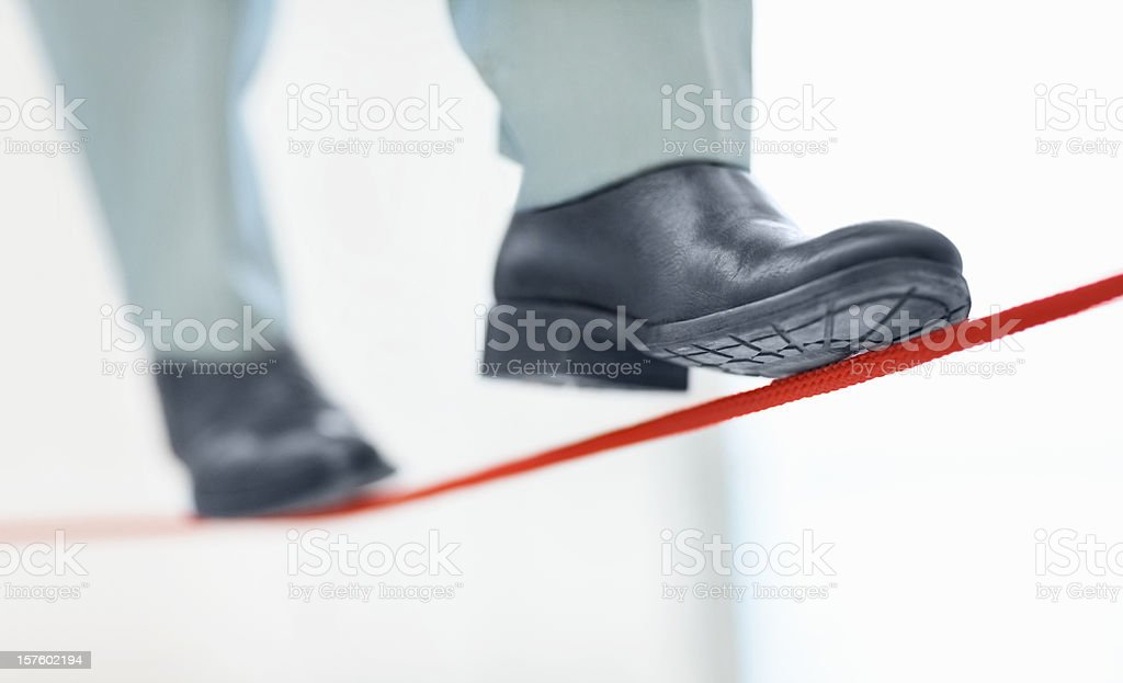 Business man walking on thin line depicting uncertainty job stock photo