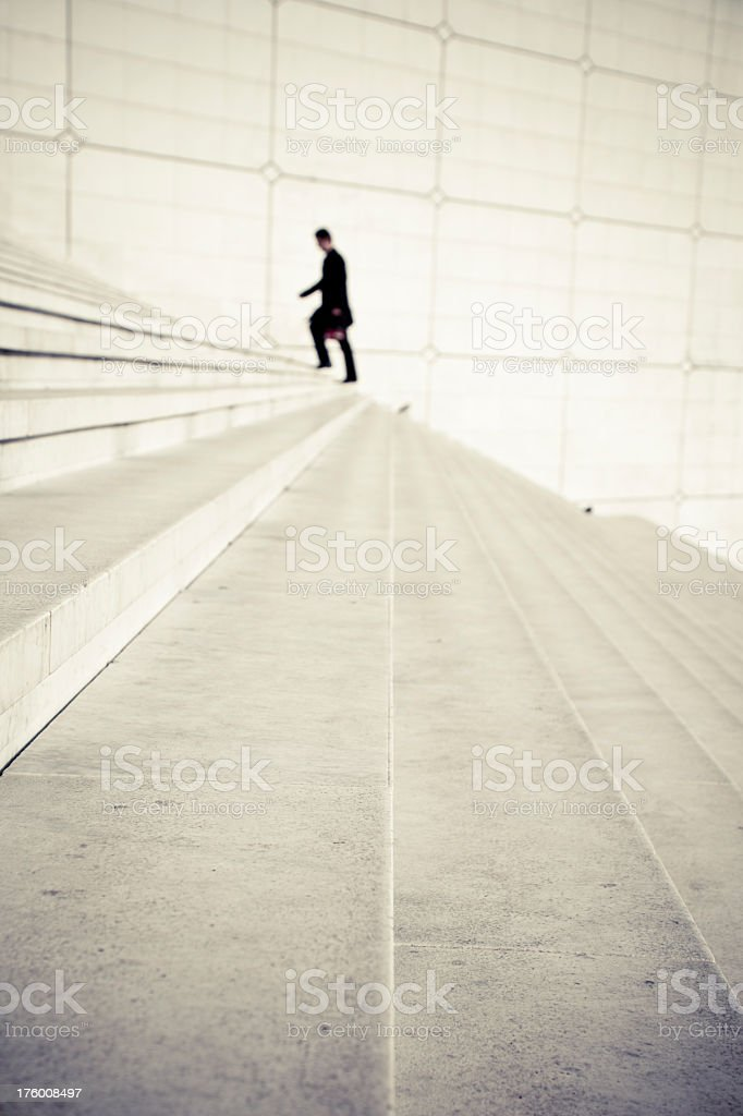 A business man walking up the steps stock photo