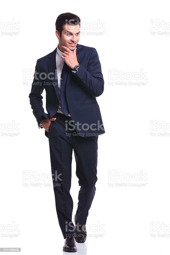 business man walking while holding one hand to his chin stock photo
